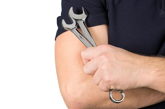 Hombre sujetando herramientas llaves de metal sobre fondo blanco.