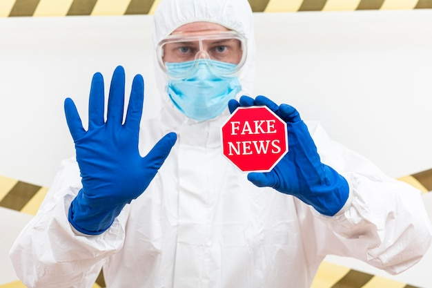Hombre sujetando insignia con noticias falsas