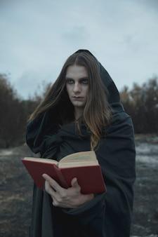 Hombre sujetando un libro de hechizos y mirando a otro lado