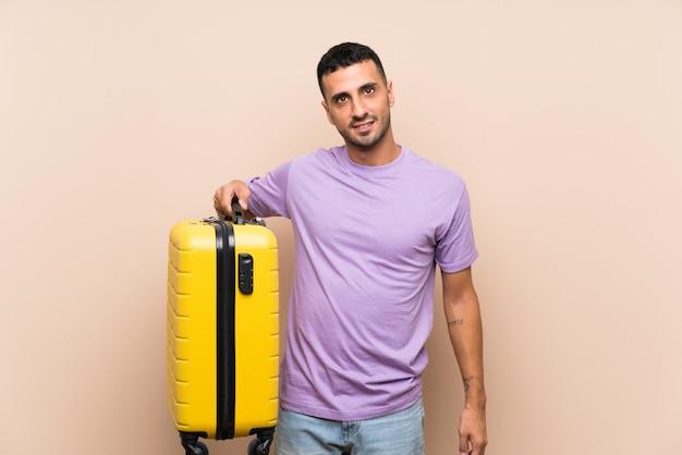 Hombre sujetando una maleta sobre pared aislada sonriendo mucho