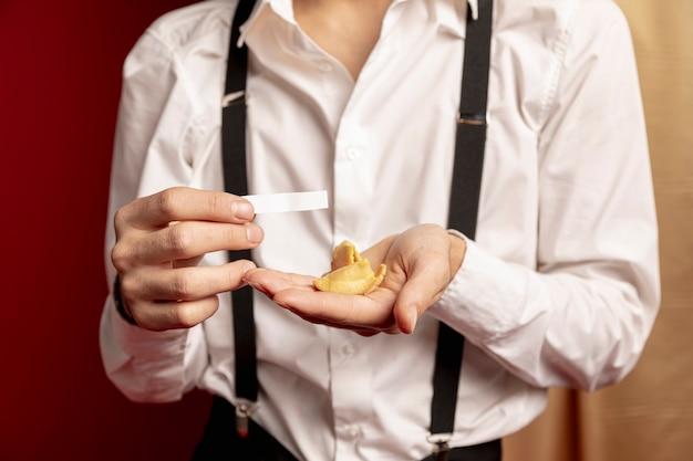 Hombre sujetando el mensaje de la galleta de la fortuna para el año nuevo chino