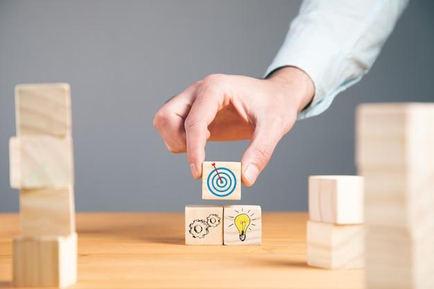 Hombre sujetando metas con idea en cubos de madera en la mesa