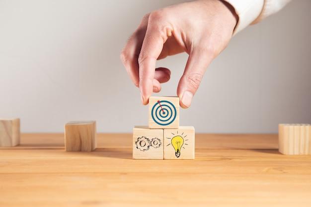 Hombre sujetando metas con idea en cubos de madera