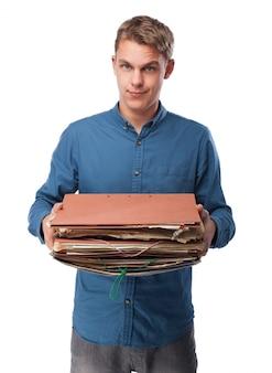 Hombre sujetando un montón de carpetas de trabajo