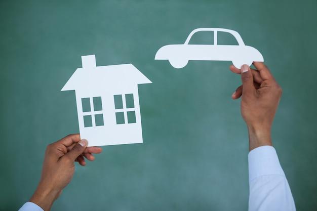 Hombre sujetando papel cortado coche y casa