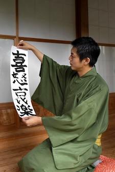 Hombre sujetando un papel con letra japonesa