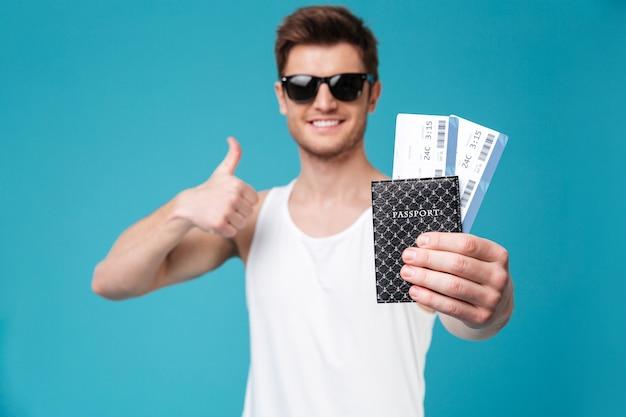 Hombre sujetando el pasaporte con boletos aéreos