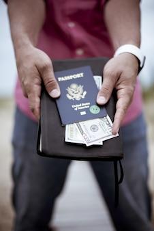Hombre sujetando el pasaporte y dinero de la biblia