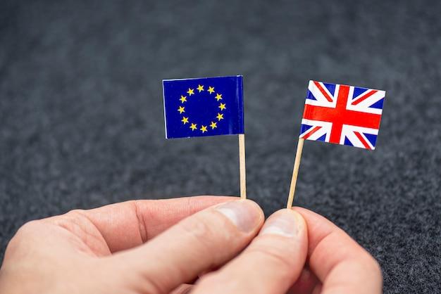 Hombre sujetando pequeñas banderas de papel de la ue y gran bretaña como símbolo de brexit, imagen conceptual