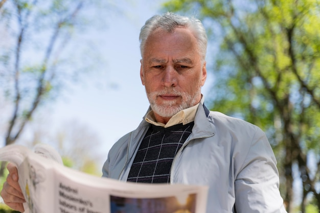 Hombre sujetando un periódico de tiro medio