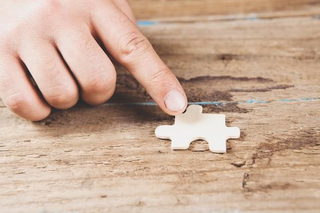 Hombre sujetando la pieza del rompecabezas en la escena de madera