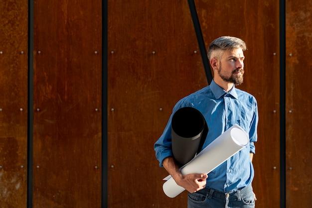 Hombre sujetando plan de construcción con espacio de copia