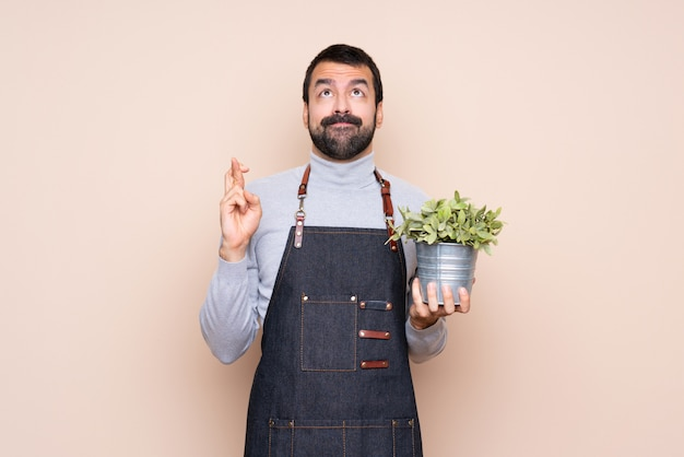 Hombre sujetando una planta con los dedos cruzados y deseando lo mejor