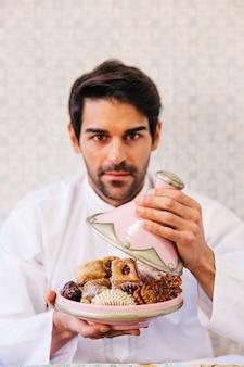 Hombre sujetando plato de comida arabe deliciosa