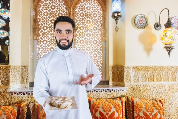 Hombre sujetando plato de comida arabe