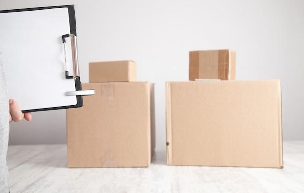 Hombre sujetando el portapapeles y bolígrafo cajas de cartón en el escritorio productos, comercio, retail, entrega