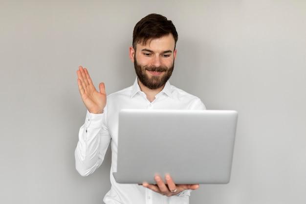 Hombre sujetando un portátil de tiro medio