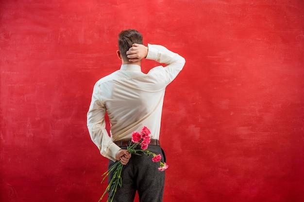Hombre sujetando ramo de claveles detrás de la espalda sobre fondo rojo studio