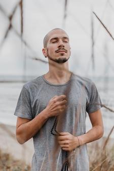 Hombre sujetando el rosario al aire libre mientras hace yoga