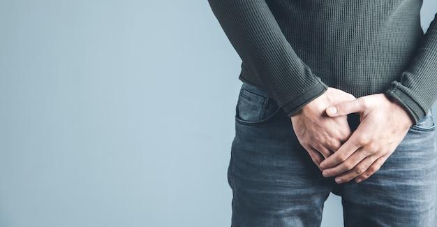 Hombre sujetando su uretra en dolor sobre fondo gris