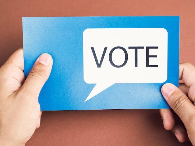 Hombre sujetando una tarjeta azul con un globo de diálogo electoral