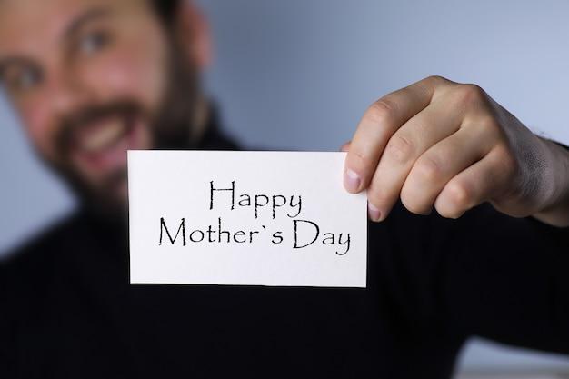 Hombre sujetando una tarjeta felicitando a las mujeres en el día de la madre