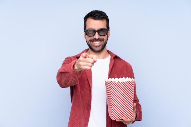 Hombre sujetando un tazón grande de palomitas de maíz sobre pared aislada
