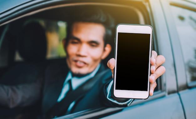 Hombre sujetando el teléfono inteligente móvil que muestra en la pantalla del teléfono y coche sentado