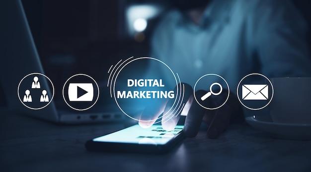 Hombre sujetando el teléfono con marketing digital en pantalla