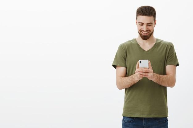 Hombre sujetando un teléfono móvil mirando la pantalla del dispositivo con una sonrisa de satisfacción, enviando mensajes o viendo videos divertidos y divertidos en línea sobre una pared blanca