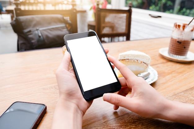 Hombre sujetando el teléfono móvil con pantalla en blanco negro en café