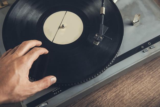 Hombre sujetando tocadiscos vintage en mesa
