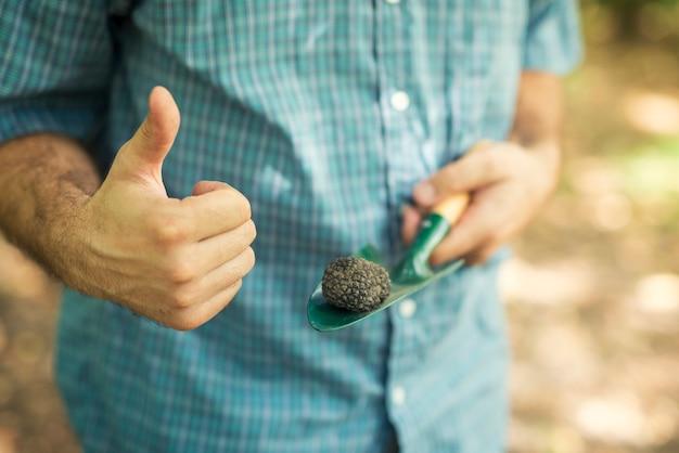 Hombre sujetando trufa negra con el pulgar hacia arriba en la naturaleza