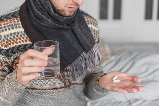 Hombre sujetando un vaso de agua y pastillas