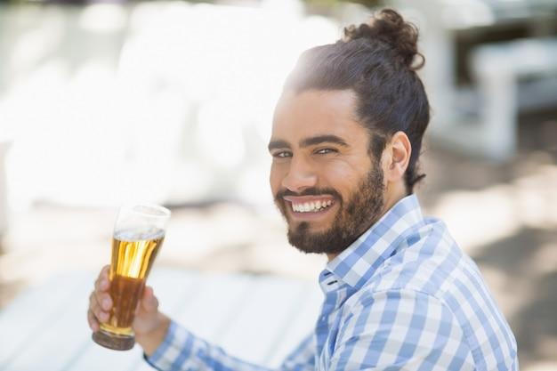 Hombre sujetando un vaso de cerveza en el parque en un día soleado