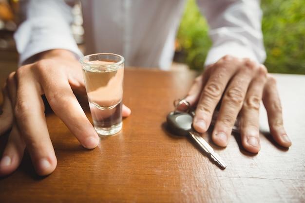 Hombre sujetando un vaso de tequila shot y la llave del coche en barra de bar