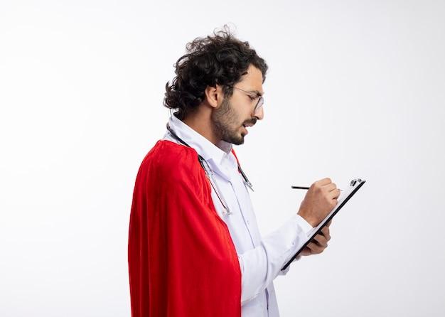 Hombre de superhéroe caucásico joven confiado en gafas ópticas con uniforme médico con manto rojo y con estetoscopio alrededor del cuello se encuentra de lado escribiendo en el portapapeles