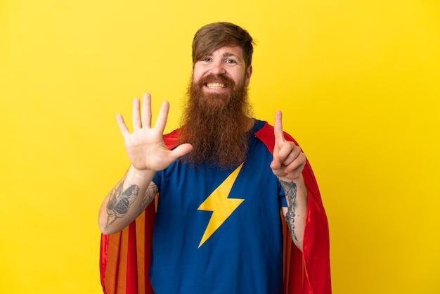Hombre de superhéroe pelirroja aislado sobre fondo amarillo contando seis con los dedos