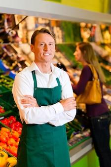 Hombre en supermercado como dependienta
