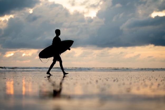 Un hombre con un surf en sus manos en la orilla del mar