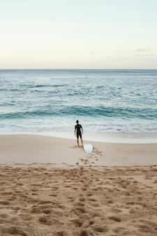 Hombre surfista mirando el tiro largo vertical del mar
