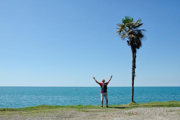 El hombre se para con sus manos en frente de una palmera alta con mar y cielo azul
