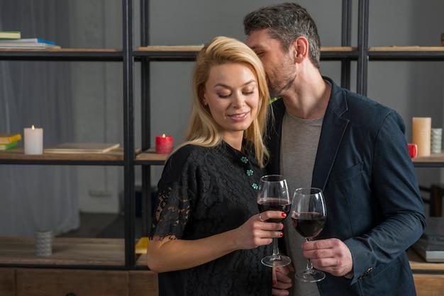 Hombre susurrando a mujer rubia con copas de vino.