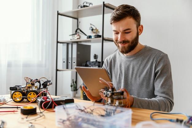 Hombre con tableta aprendiendo a hacer robot