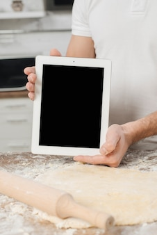 Hombre con tableta en cocina