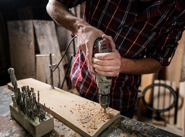 Hombre con taladro trabajando con madera Foto gratis
