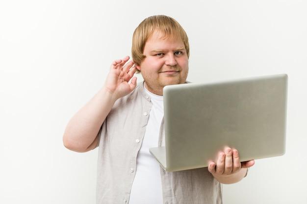 Hombre de talla grande del cáucaso sosteniendo una computadora portátil tratando de escuchar un chisme.