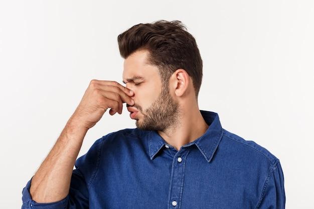 Hombre tapándose la nariz contra un mal olor aislado sobre gris