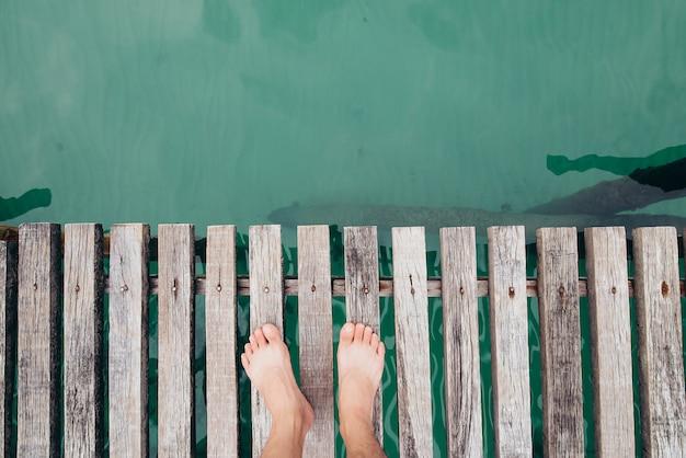 Hombre con tarifa desnuda en un puente de madera, vista desde arriba