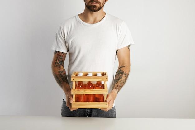 Hombre tatuado y barbudo sosteniendo una pequeña caja con seis botellas de vidrio sin marcar de bebida de cerveza artesanal en la pared blanca